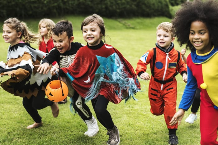 Kids running with halloween costumes on for alternative trick-or-treating