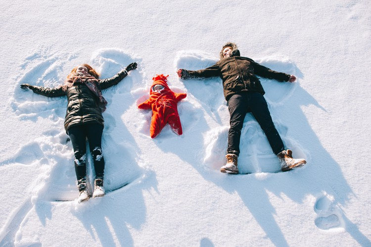 family making snow angels on a cold winter vacation