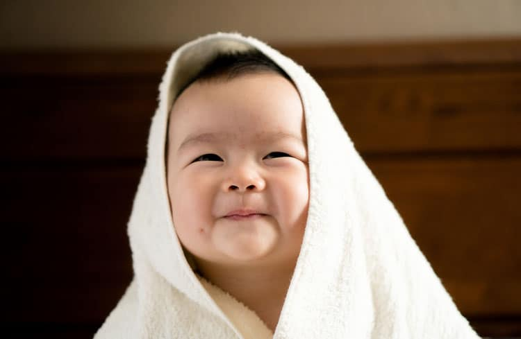 happy baby wrapped in towel