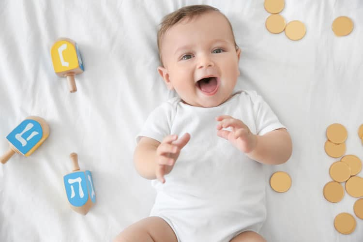 baby surrounded by hanukkah items
