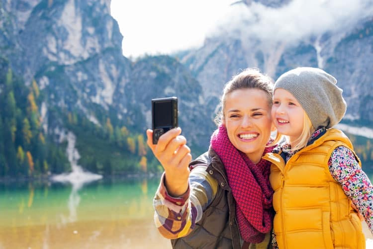 mom and daughter taking selfie on single parent travel vacation
