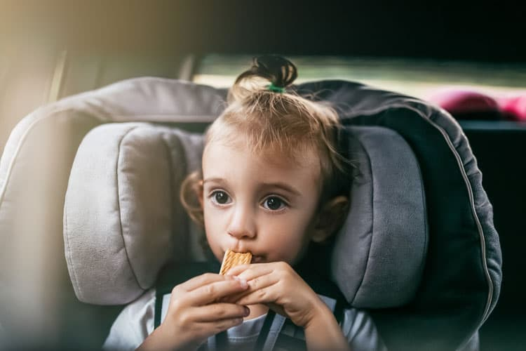 girl eating snack on a road trip
