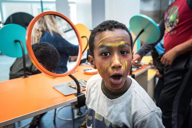 Boy painting face at Minnesota Children's Museum