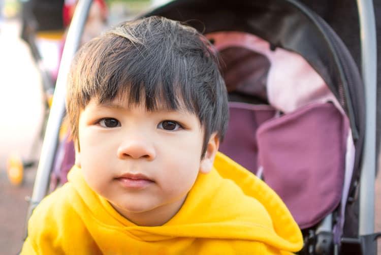 boy sitting in a stroller at Disney World