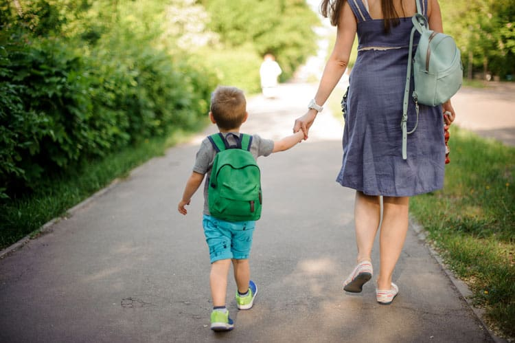 boy walking to kindergarten with his mom