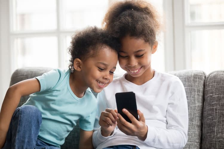 two children looking at mobile phone