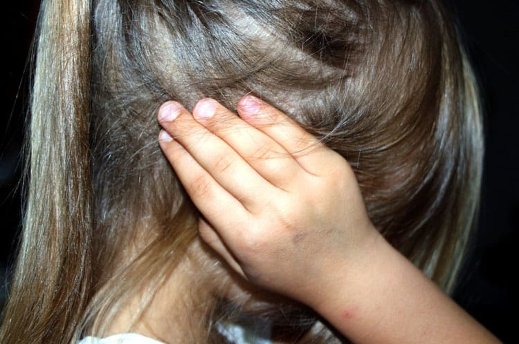 child covering her ears