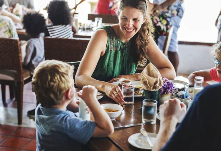 family eating at hotel restaurant during family travel