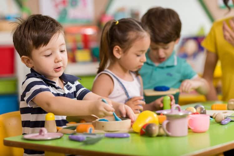 children sitting at table practicing the montessori method