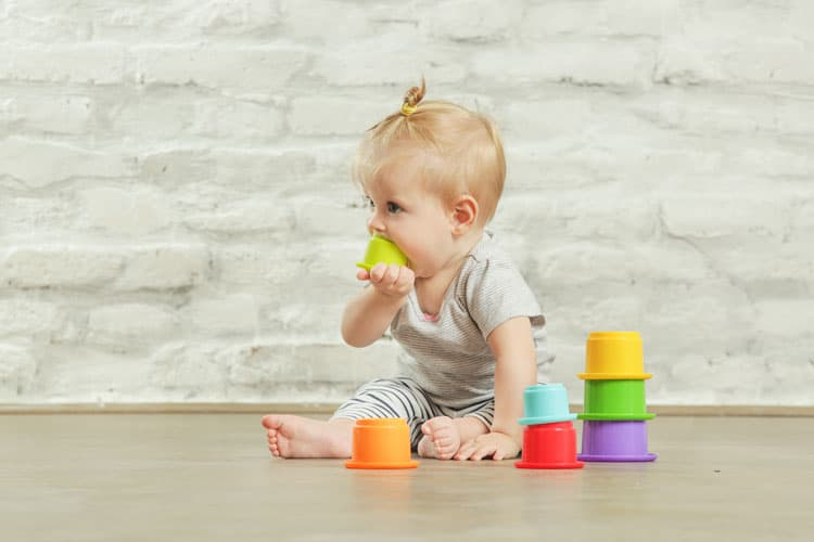 baby with toy in her mouth